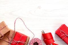 Preparando per la festa - spostamento di regalo in carta da imballaggio rossa e beige fotografia stock