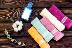 Preparando per la lavanderia con il detersivo e gli asciugamani sulla vista superiore del fondo di legno immagine stock