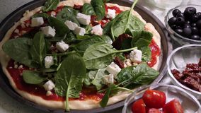 Preparando a pizza que toping Colocando as folhas frescas do spinache na cobertura da pizza filme