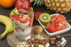 Preparando prima colazione sana per i bambini Yogurt con la farina d'avena, la frutta, i dadi ed il cioccolato Farina d'avena per Fotografia Stock