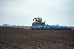 Preparando a terra e fertilização Cultivador da sementeira nas terras fotos de stock royalty free