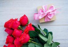 Preparando um presente, em uma tabela de madeira, com rosas Mão fêmea que guarda um presente, envolvido com fita, em um fundo do  fotos de stock
