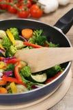 Preparando vegetais do alimento do vegetariano em cozinhar a bandeja com espátula foto de stock royalty free