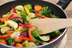Preparando verduras de la comida en cocinar la cacerola con la espátula Foto de archivo libre de regalías
