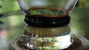 Preparar el café con leche usando un filtro tradicional vietnamita del phin en café Los goteos del café caen lentamente en una ta metrajes