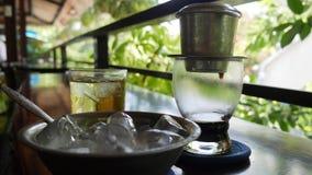 Preparar el café sólo usando un filtro tradicional vietnamita del phin en café Los goteos del café caen lentamente en una taza de almacen de metraje de vídeo