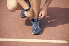 Preparar-se a movimentar-se M?os que amarram o fundo da pista de atletismo da sapatilha dos la?os M?os do desportista com pod?met imagem de stock