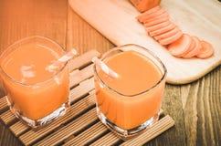 Preparar-se para dois vidros que bebem a cenoura/preparar-se para dois vidros que bebem a cenoura em um fundo de madeira toned foto de stock