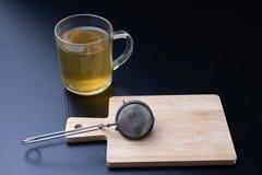 Preparar té en una tabla negra Taza con una bebida caliente imagen de archivo