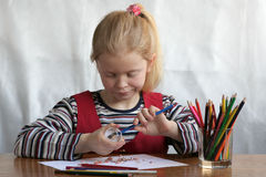 Preparation. A little girl sharpening her crayons Royalty Free Stock Images