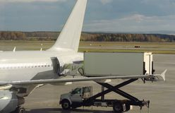 Preparation of the aircraft, a car with a hydraulic elevator delivers public catering to the plane. photo for drawing. The necessary logistic companies stock images