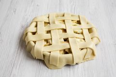 Preparation of apple pie on white wooden background, low angle view. Close-up.  stock photography