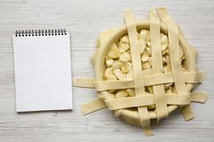 Preparation of apple pie on a white wooden table, top view. Blank notepad. Flat lay, overhead, from above.  stock photo