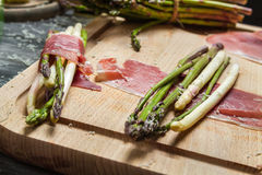 Preparation asparagus with prosciutto ham and cheese royalty free stock photography