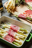 Preparation of asparagus wrapped in Parma ham with cheese Stock Photography
