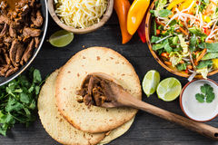Preparation authentic mexican tacos, top view. Overhead view on authentic mexican street taco with beef and vegetables from above on wooden table Stock Photography