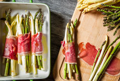 Preparation baked asparagus with prosciutto royalty free stock photography