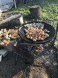 Preparation of baked potatoes with bacon. Potatoes and lard are on the grill. The fire is burning, the coals are smoldering. Preparation of baked potatoes with Royalty Free Stock Photography