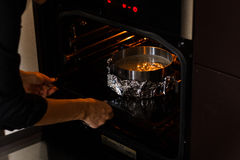Preparation baking the pie. Man`s hands puts form with the batter into the oven. Stock Photo