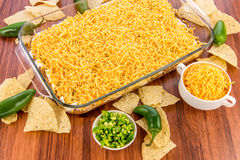 Preparation of bean dip with jalapenos, sour cream and cheddar c. Preparation of layered bean dip with jalapenos, sour cream and cheddar cheese Royalty Free Stock Photography