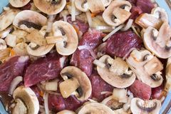 Preparation of beef with mushrooms and onions. Raw meat.  Stock Images