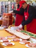 Preparation of big mortadella sandwich. ZAGREB, CROATIA - FEBRUARY 16, 2014: Promotion of Mortadella salami on Ban Jelacic square in Zagreb. Two cooks preparing Royalty Free Stock Photos