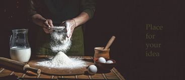Preparation of bread dough. Bakery, baker`s hands, flour is poured, flying flour. Toned stock photography