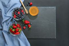 Preparation for breakfast with variety of berries and honey on black background and copy space. Preparation for breakfast on a black stone board in two bowls Royalty Free Stock Image