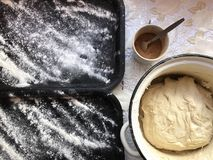 Preparation of buns with cinnamon at home. The tray is sprinkled with flour, dough and a wooden rolling pin lie on the table. Stock Photography