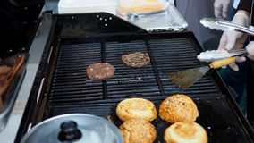 A preparation of burger beef barbecuing on a hot gas stove. stock images