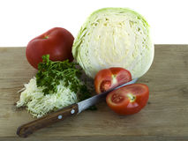 Preparation of cabbage salad with tomato and herbs. Are located on wooden board Stock Photos