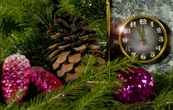 Preparation for the celebration of Christmas or New Year holiday. Vintage clock in a gray stone block with brass details showing five minutes to twelve on the Stock Photo