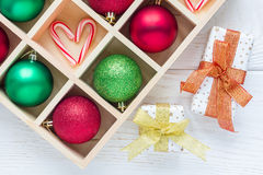 Preparation for Christmas: festive balls and candy cane in wooden box, gifts on white wooden table Stock Photography