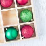 Preparation for Christmas: festive balls and candy cane in wooden box on a white table, square format. Preparation for Christmas: festive balls and candy cane in royalty free stock images