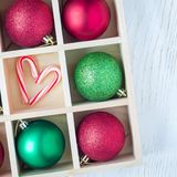 Preparation for Christmas: festive balls and candy cane in wooden box on white table, square. Format royalty free stock photography