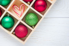 Preparation for Christmas: festive balls and candy cane in wooden box on white wooden table, copy space Royalty Free Stock Photos