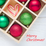 Preparation for Christmas: festive balls and candy cane in wooden box on white wooden table, square format,text. Preparation for Christmas: festive balls and stock photos