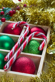 Preparation for Christmas: festive balls and candy cane in wooden box on white wooden table Royalty Free Stock Images