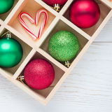 Preparation for Christmas: festive balls and candy cane in wooden box on wooden table, square format, copy space Royalty Free Stock Photo