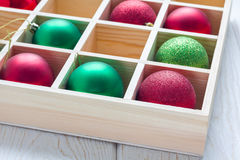 Preparation for Christmas: festive balls in wooden box on white wooden table Stock Photography