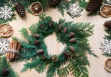 Preparation for Christmas holiday. Christmas composition of wreath, decor, dry orange, twigs and snowflakes. Stock Photos