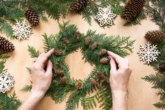 Christmas composition of wreath, decor, dry orange, twigs and snowflakes. Woman prepare a wreat Royalty Free Stock Image