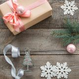 Preparation for Christmas holiday. Christmas gift box with pink ribbon and ball, decor from snowflakes, silver ribbon and decor ar Stock Image