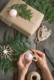 Christmas Still life of giftbox, decor, twine, fir tree, twigs. Woman prepare a gift. Top view Stock Photography