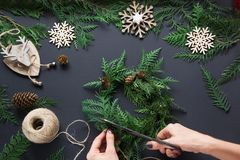 Preparation for Christmas holiday. Christmas workshop of wreath, decor, twine, twigs and snowflakes. Woman prepare a wreath. Top v royalty free stock photography