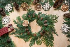 Preparation for Christmas holiday. Christmas composition of wreath, decor, dry orange, sleigh and snowflakes. Top view and copy sp Royalty Free Stock Images