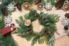 Preparation for Christmas holiday. Christmas composition of wreath, decor, dry orange, sleigh and snowflakes. Top view and copy sp Royalty Free Stock Photo