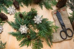 Preparation for Christmas holiday. Christmas composition of wreath, decor, dry orange, twigs and snowflakes. Woman prepare a wreat Stock Photo