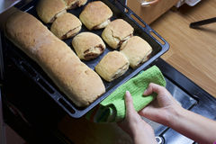 Preparation of cinnamon rolls. The woman takes a baking sheet out of the oven. There are ready buns and a roll with cinnamon on it Stock Image