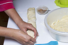 Preparation of cinnamon rolls. The woman turns off the dough with a filling of cinnamon and sugar. Preparation of cinnamon rolls. The woman turns off the dough stock photos
